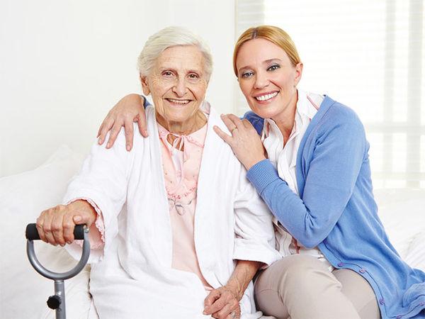 Jüngere Frau betreut ältere Dame - beide sind fröhlich und lächeln nett in die Kamera.